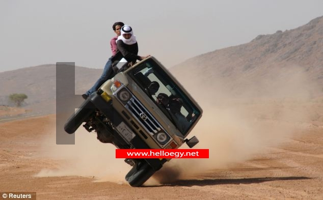 Daredevil Saudi Arabian craze of 'sidewalk skiing' brings new meaning to the term 'off-road' as drivers flip car onto just two wheels as passengers cling on outside